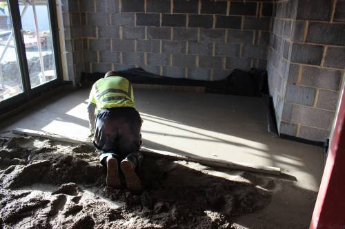 Screed is compacted and levelled across the whole interior