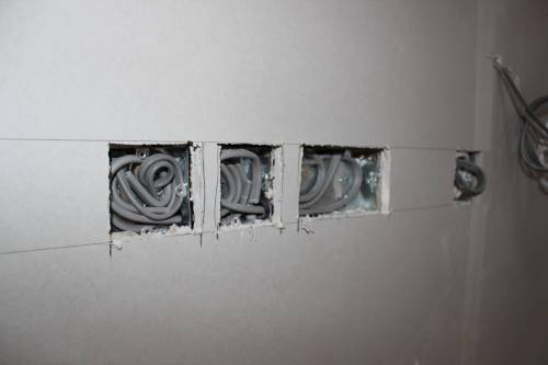 Plasterboard cut around sockets and switches in the kitchen