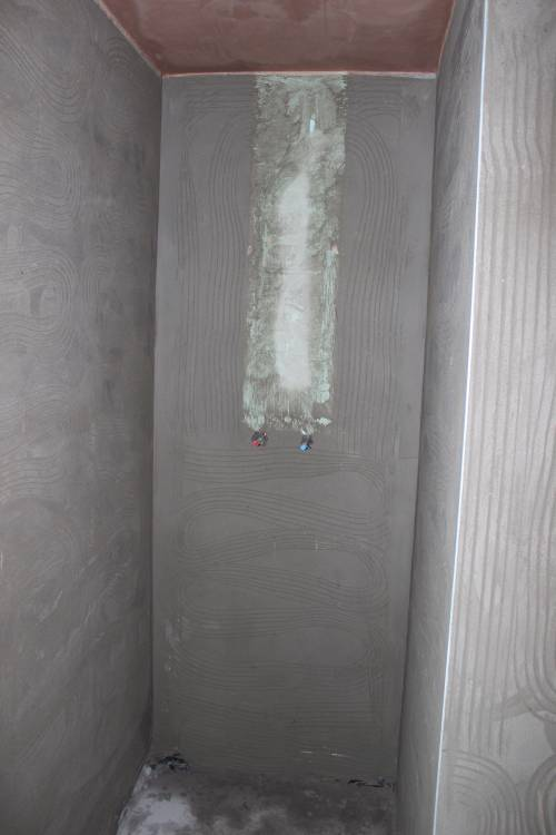 Shower cubicle with hot and cold water supply pipes