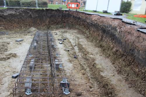 It will strengthen the footing for the larger retaining wall
