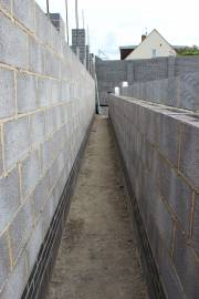 Back alley separating the house and the retaining wall