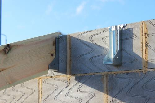 Stainless steel brackets for locating trusses against the external walls