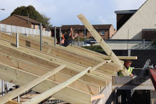 Carpenters in action getting one of the roof trusses into place
